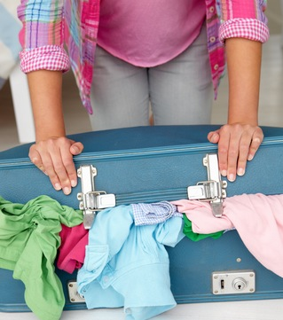 Teenage girl struggling to close suitcase